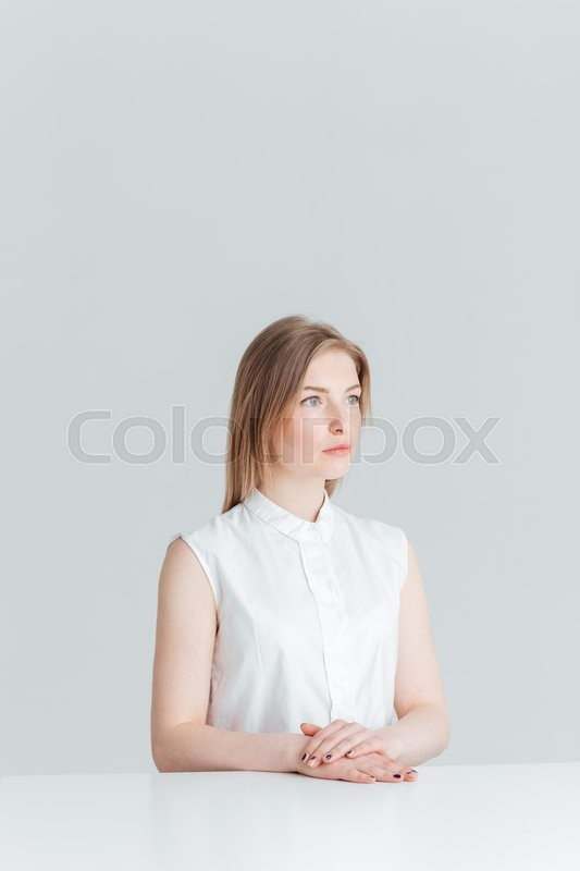Stock image of 'Thoughtful young woman sitting at the table isolated on a white background'