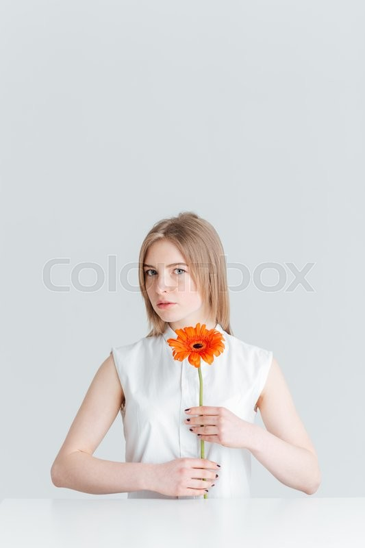 Stock image of 'Beauty portrait of attractive blonde woman sitting at the table and holding flower isolated on a white background'
