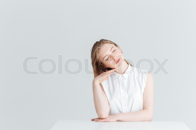 Stock image of 'Beautiful woman sitting at the table with closed eyes isolated on a white background'