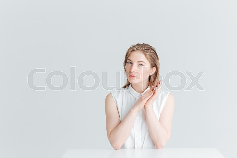 Stock image of 'Charming young woman sitting at the table and looking at camera isolated on a white background'