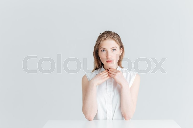 Stock image of 'Beautiful woman sitting at the table and looking at camera isolated on a white background'