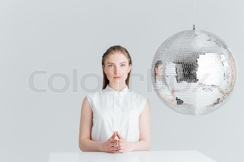 Stock image of 'Attractive woman sitting at the table near mirror ball and looking at camera isolated on a white background'