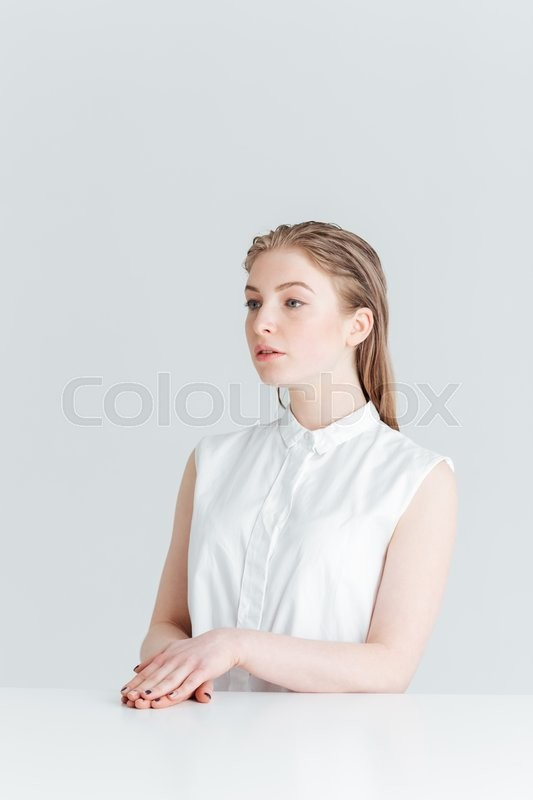 Stock image of 'Charming woman sitting at the table and looking away isolated on a white background'