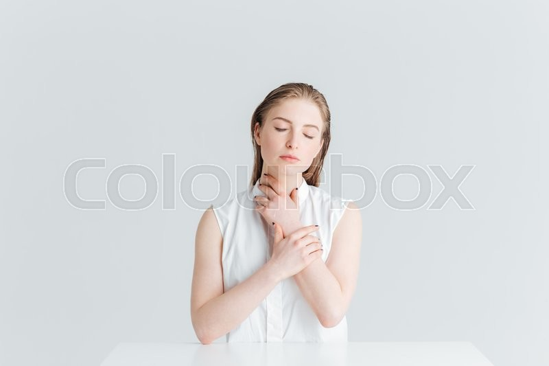 Stock image of 'Relaxed woman sitting at the table with closed eyes isolated on a white background'