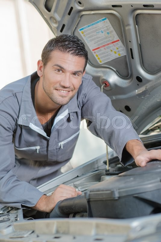 Stock image of 'Mechanic stood by a car'