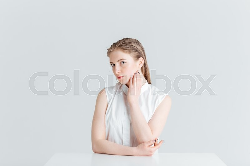 Stock image of 'Beauty portrait of a lovely woman sitting at the table and looking at camera isolated on a white background'