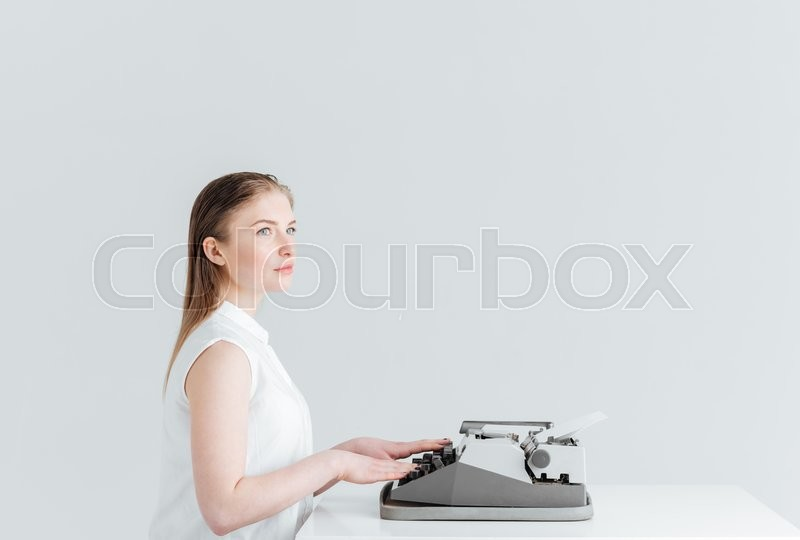 Stock image of 'Pensive woman typing on retro machine isolated on a white backgound'