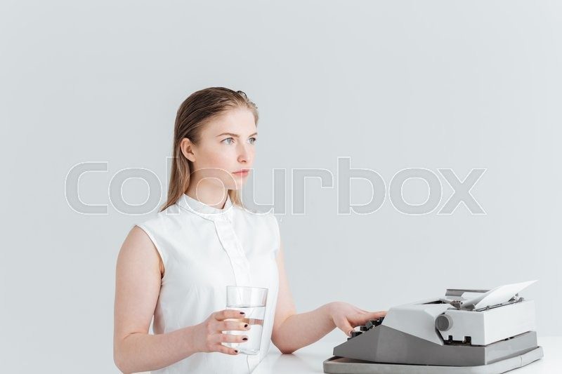 Stock image of 'Young woman worrking on retro print machine and holding glass with water isolated on a white background'
