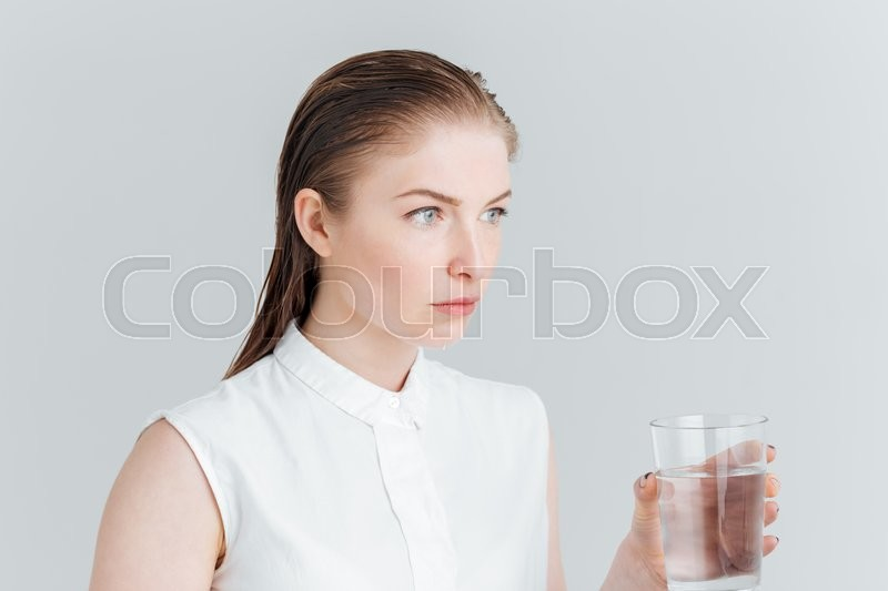 Stock image of 'Beauty portrait of a thoughtful woman holding glass with water isolated on a white background'