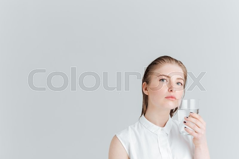 Stock image of 'Beauty portrait of a pensive woman holding glass of water isolated on a white background'