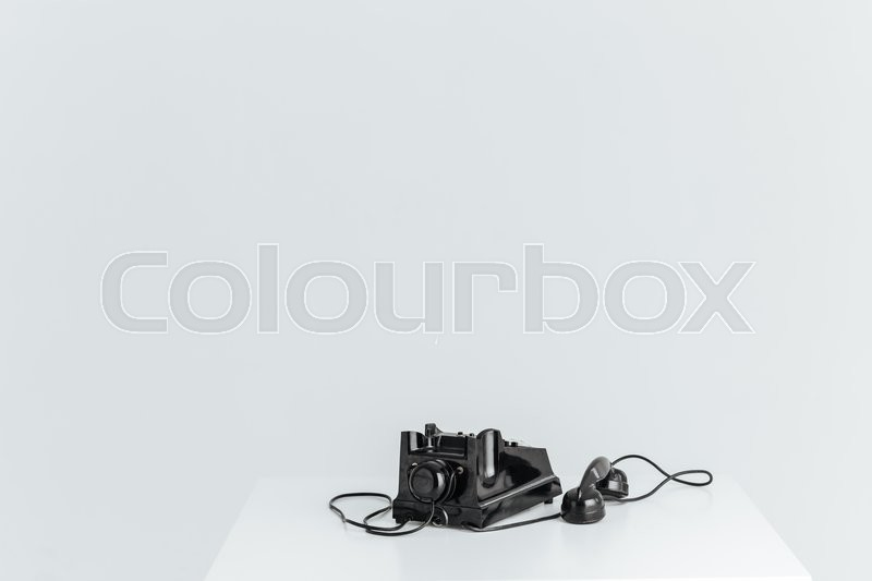 Stock image of 'Closeup portrait of a retro telephone on the table isolated on a white background'