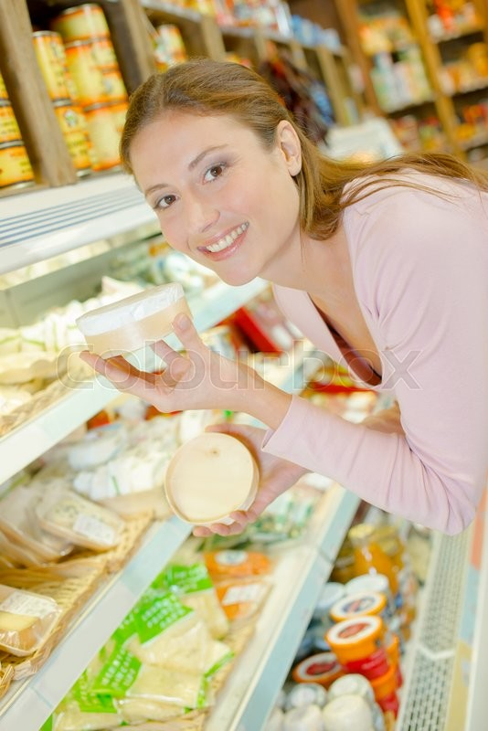 Stock image of 'Woman stood by the cheese aisle'