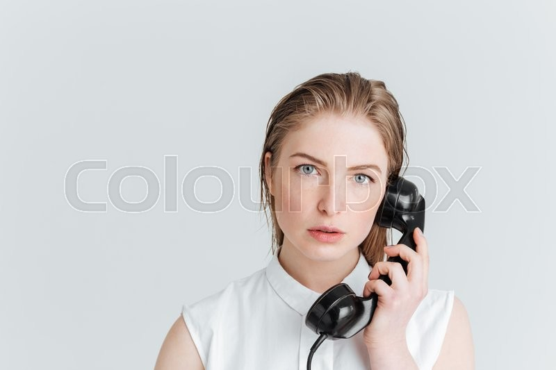 Stock image of 'Young woman talking on retro tube isolated on a white background'
