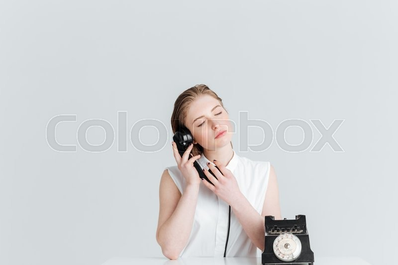 Stock image of 'Relaxed woman with closed eyes speaking on retro phone isolated on a white background'