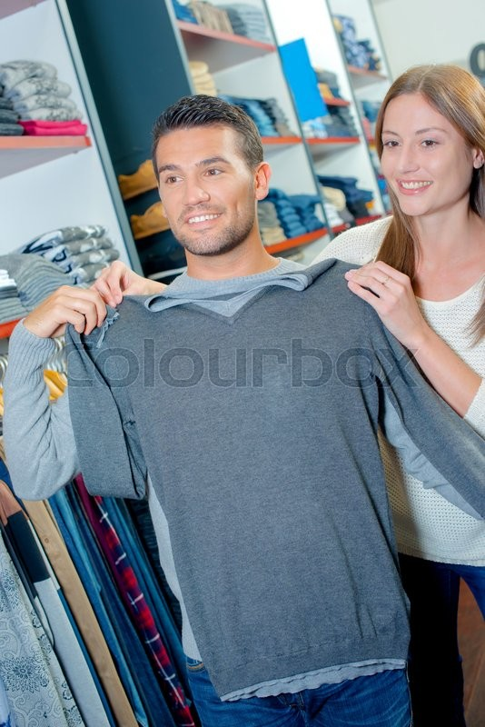 Stock image of 'Couple in clothes shop, holding jumper against man'