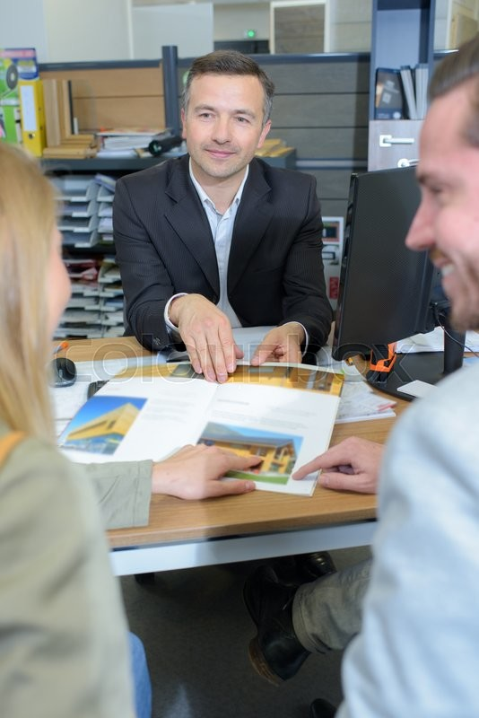 Stock image of 'Salesman showing housing brochure to couple'