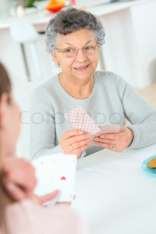 Stock image of 'Old lady playing a card game'