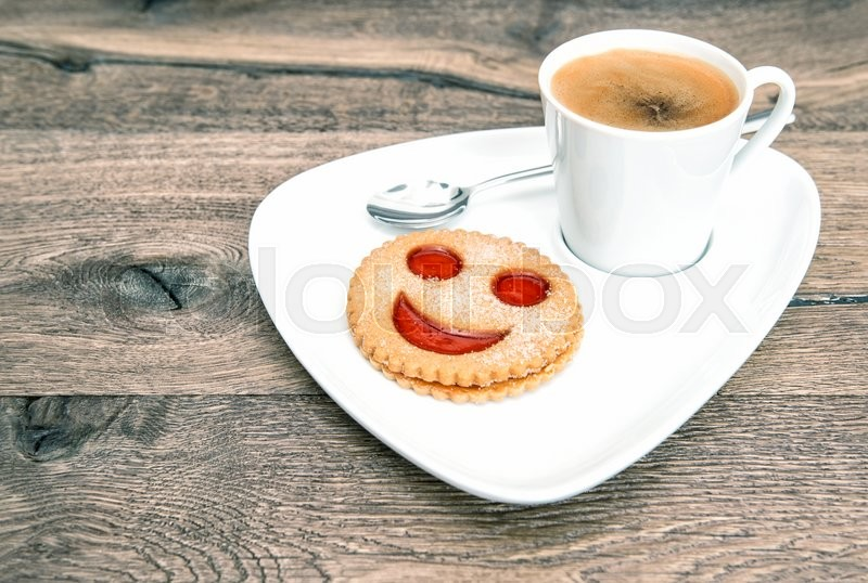 Stock image of 'Cup of coffee with smiley face cookie on wooden background. Funny breakfast'