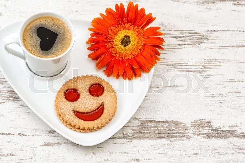 Stock image of 'Cup of black coffee with smiled cookie on wooden background. Heart, love, flower'