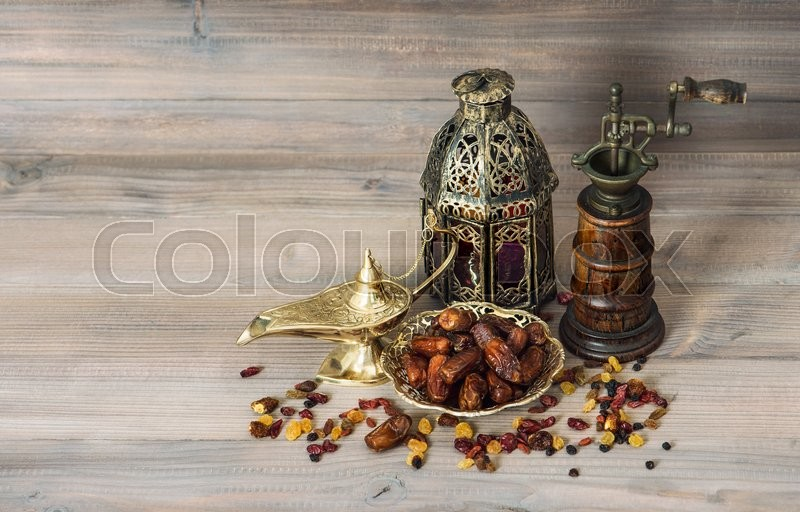 Stock image of 'Vintage oriental table decoration latern and mill. Raisins and dates on wooden background'