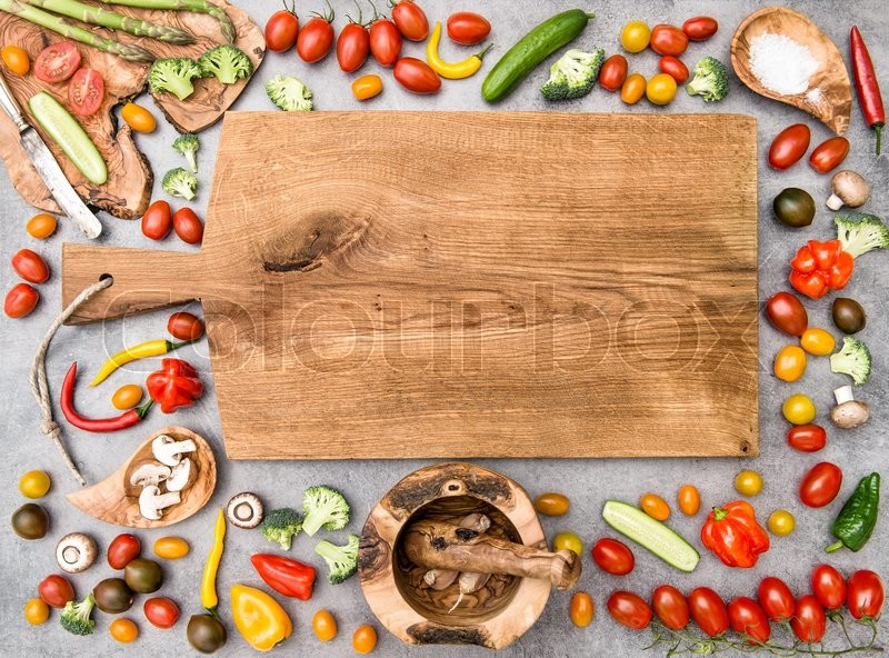 Stock image of 'Wooden cutting board and fresh vegetables and on kitchen table. Organic eating. Vegetarian food. Healthy cooking'