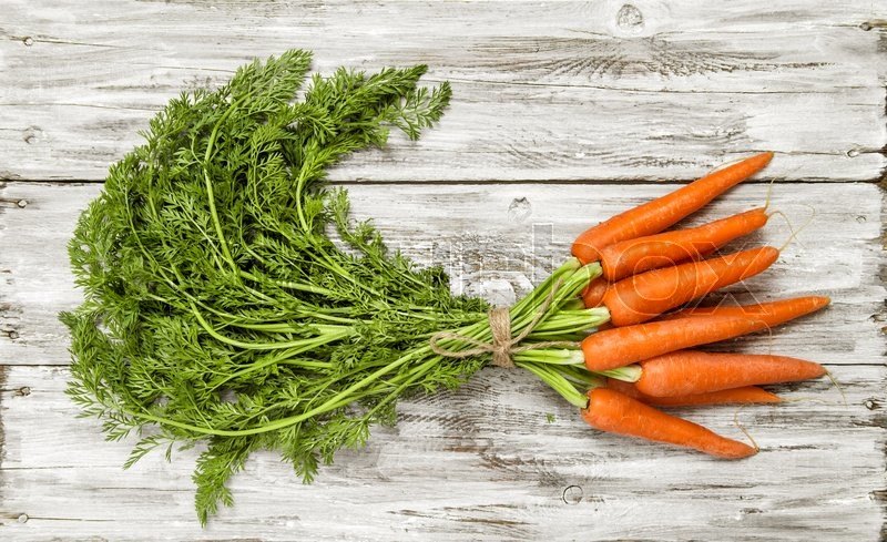Stock image of 'Carrots bunch on bright rustic wooden background. Organic food concept'