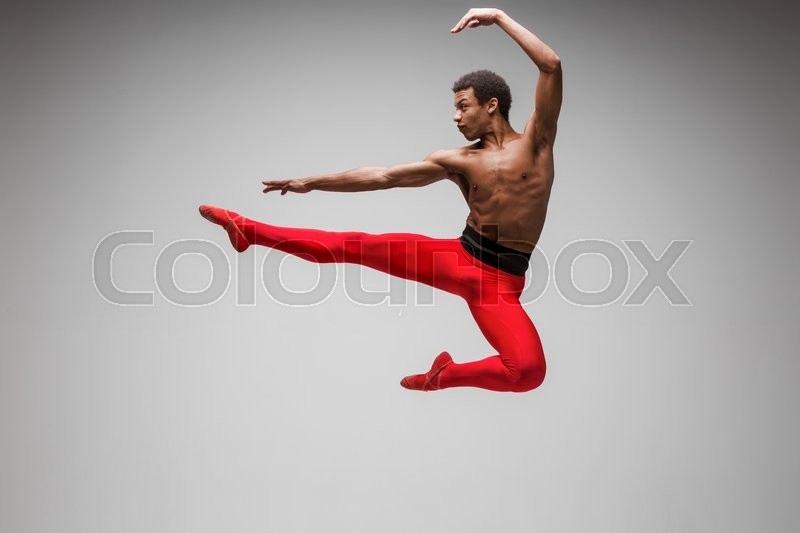 Stock image of 'Young and stylish modern ballet dancer jumping on gray background'