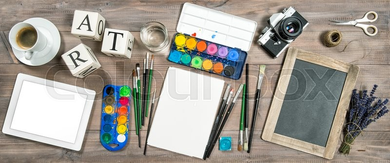 Stock image of 'Artistic workplace. Watercolor, brushes, digital tablet pc, chalkboard, vintage no name camera, office supplies, tolls and accessories'