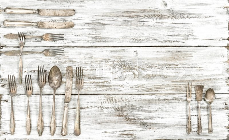 Stock image of 'Antique cutlery on rustic wooden background. Retro kitchen utensils knife, fork and spoons'