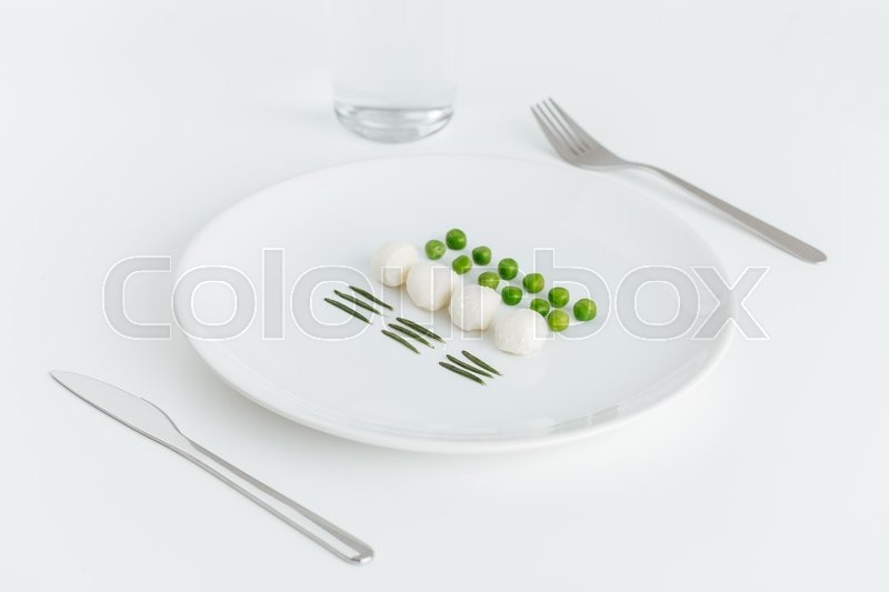 Stock image of 'Green peas, rosemary and balls of mozzarella on the plate over white background'