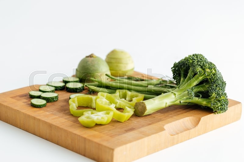 Stock image of 'Fresh green vegetables on wooden board over white background'