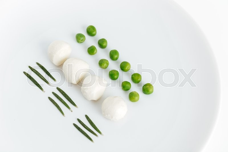 Stock image of 'Herbs, green peas and mozzarella on the plate'