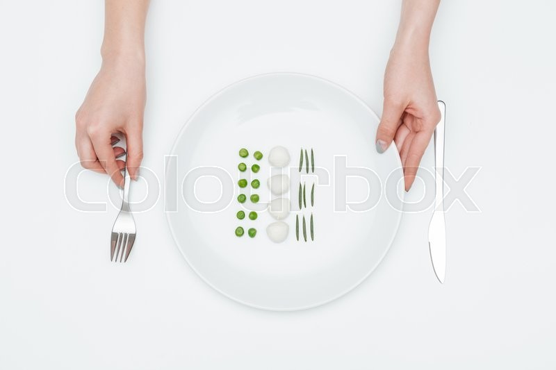 Stock image of 'Hands of young woman holding fork and plate with green peas, mozzarella and herbs over white background'