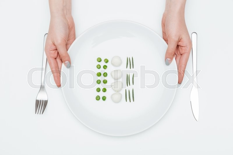 Stock image of 'Hands of young woman holding plate with green peas, mozzarella and herbs over white background'