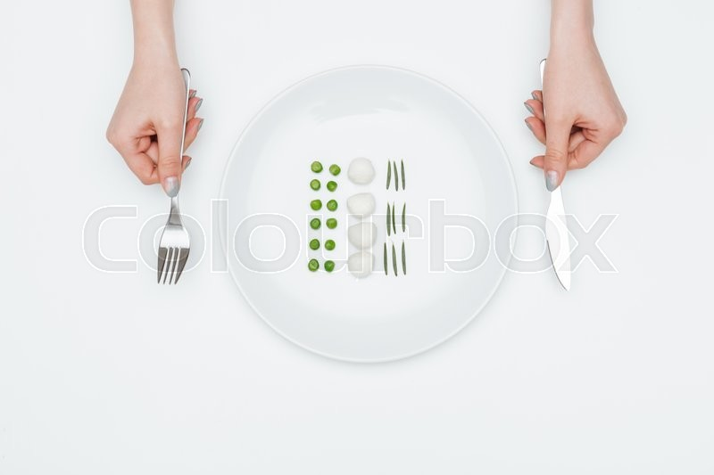 Stock image of 'Top view of plate with green peas, mozzarella and herbs and hands holding fork and knife over white background'