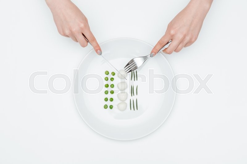 Stock image of 'Top view of hands of young woman eating green peas, mozzarella and herbs using fork and knife over white background'