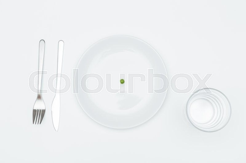 Stock image of 'Top view of plate with one green pea, glass of water? fork and knife over white background'