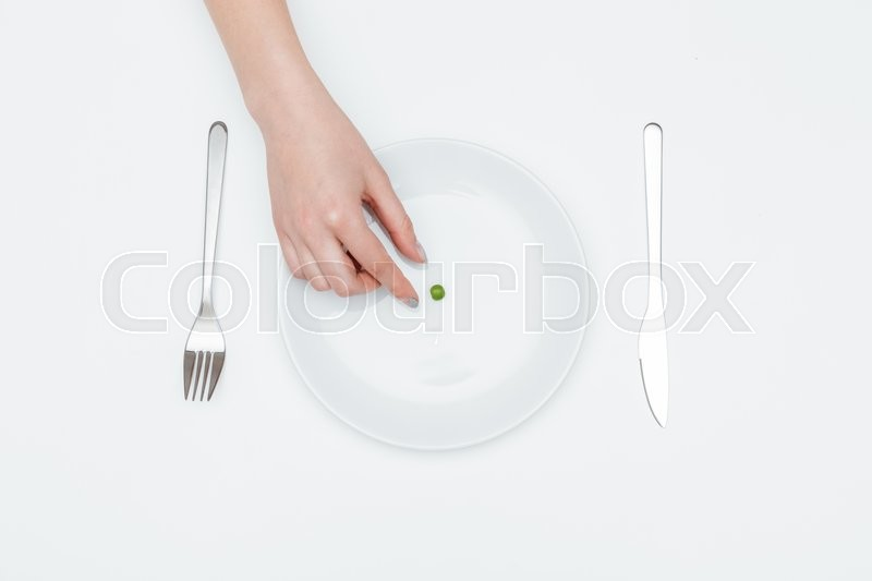 Stock image of 'Top view of young woman hand taking one green pea from the plate over white background'