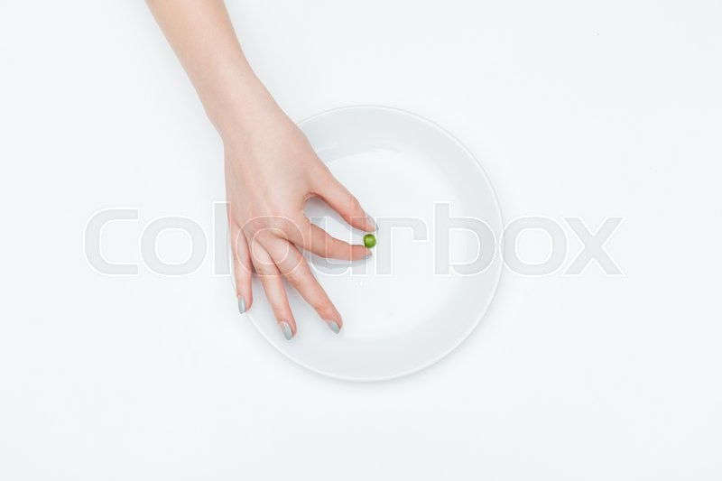 Stock image of 'Closeup of hand of young woman taking one small green pea from the plate over white background'