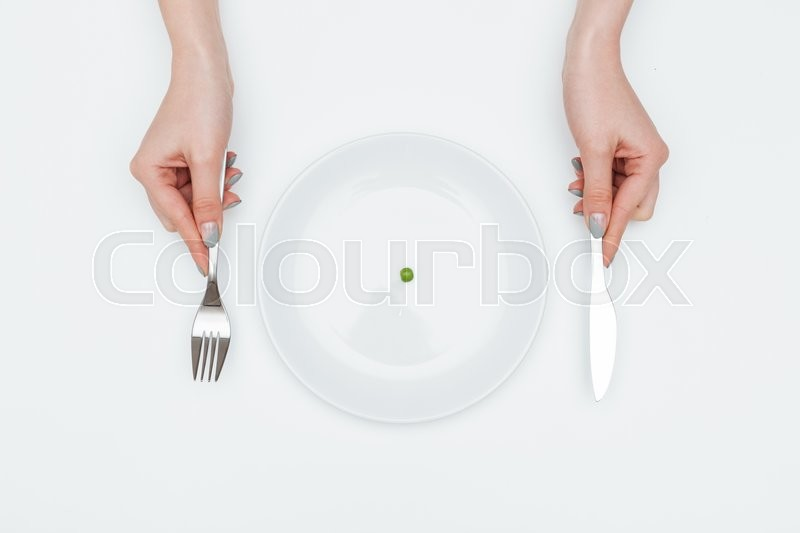 Stock image of 'Closeup of hands of young woman eating one small green pea using knife and fork over white background'