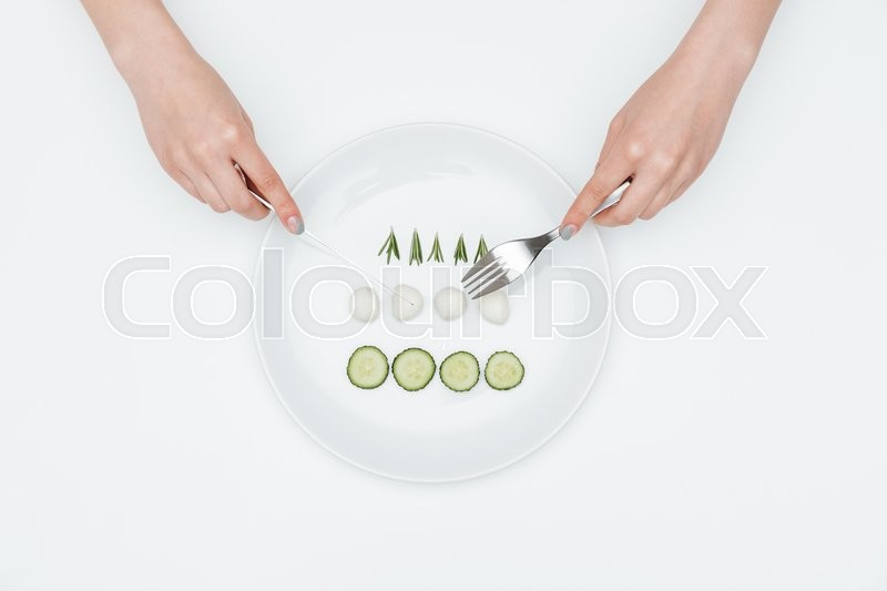 Stock image of 'Top view of hands of young woman eating cucumber, mozzarella and herbs using fork and knife over white background'