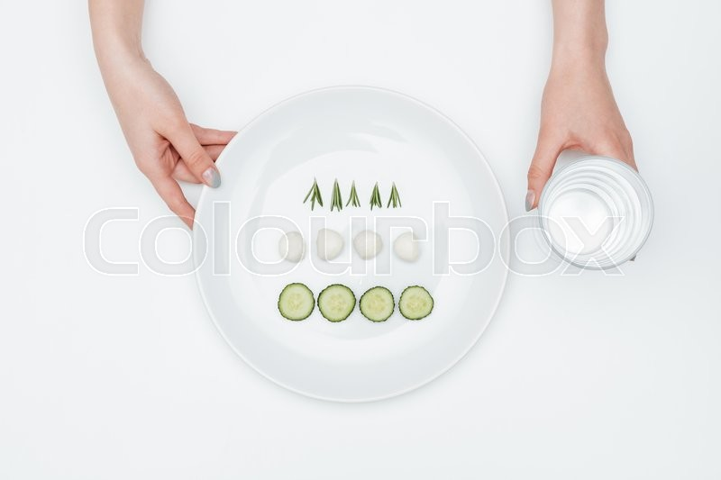 Stock image of 'Two hands holding glass of water and plate with cucumber, mozzarella and herbs over white background'