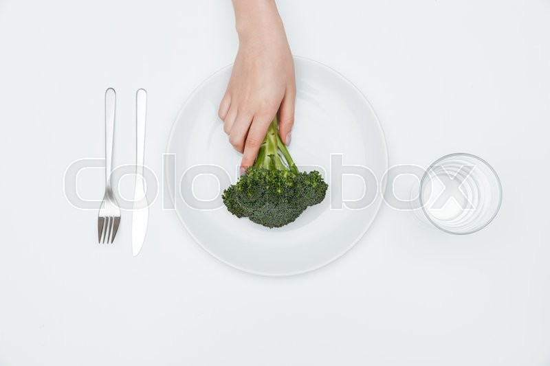 Stock image of 'Top view of woman hand taking broccoli from plate over white background'
