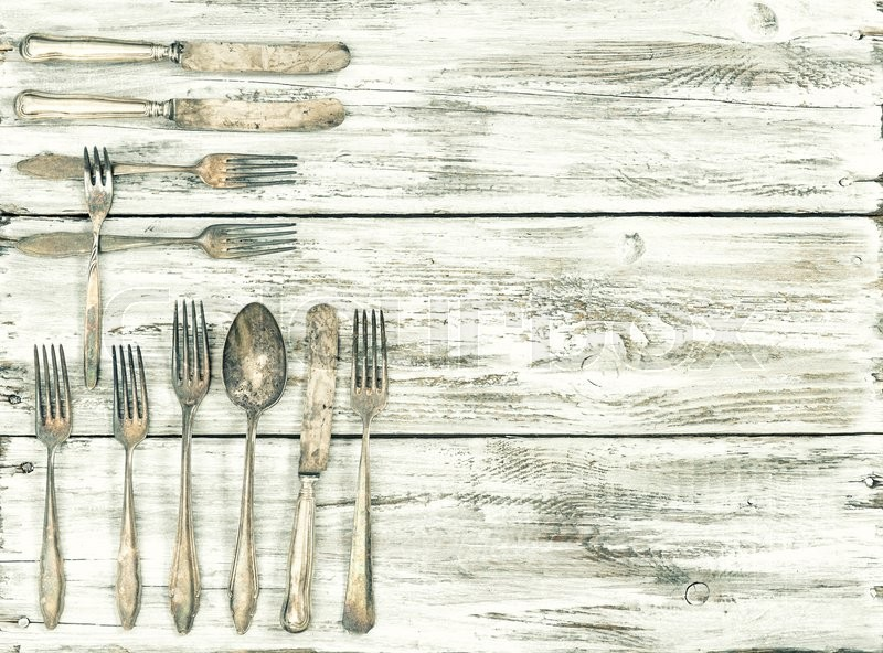 Stock image of 'Antique cutlery on rustic wooden background. Retro kitchen utensils. Vintage style toned picture'