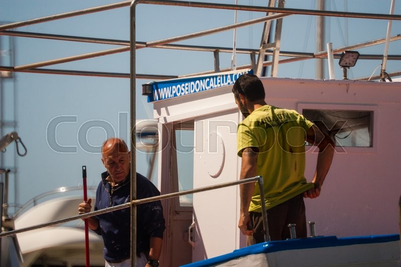 Editorial image of 'Palamos, Catalonia, may 2016_fisherman cleaning and repairing motorboat'