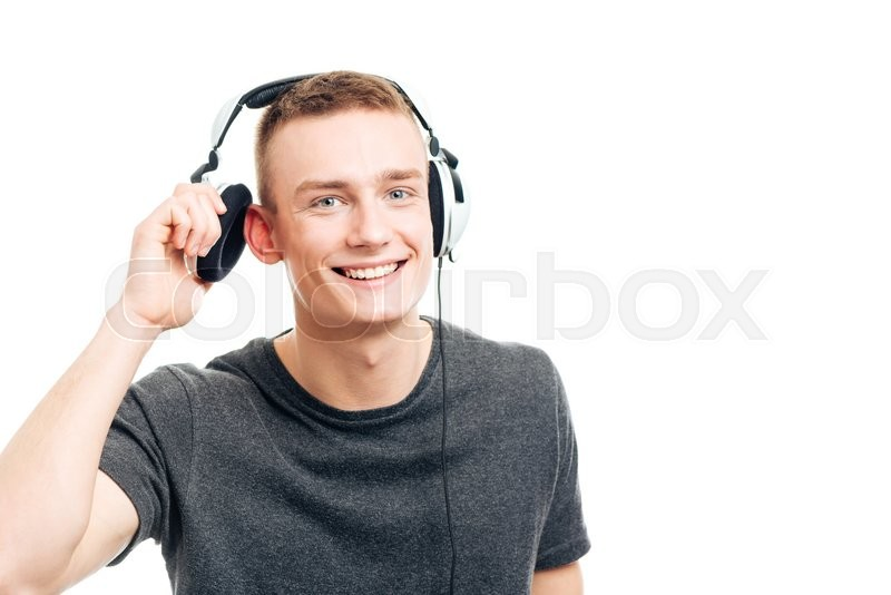 Stock image of 'Happy casual man listening music in headphones and looking at camera isolated on a white background'