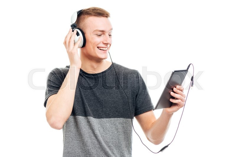 Stock image of 'Smiling casual man using tablet computer with headphones isolated on a white background'