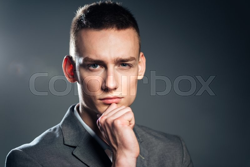 Stock image of 'Pensive businessman looking at camera over gray background'
