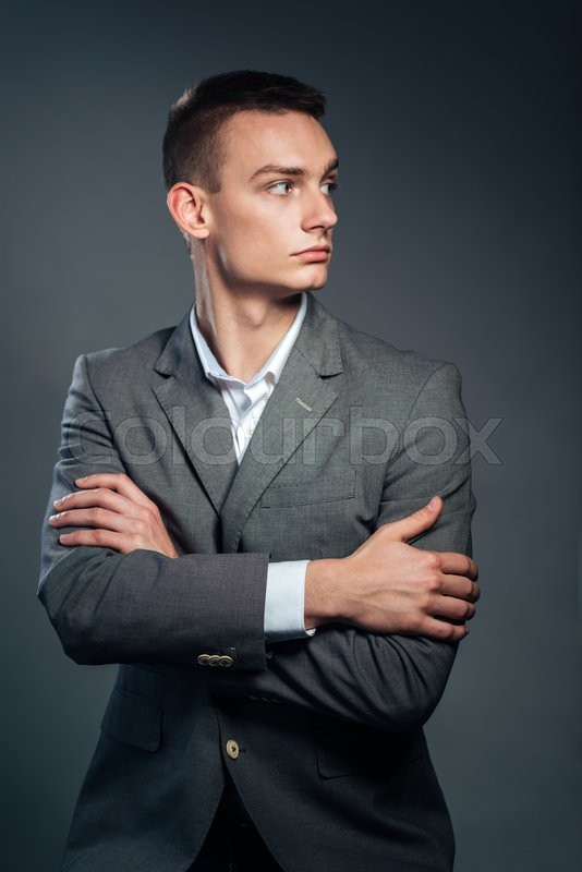 Stock image of 'Serious businessman standing with arms folded over gray background and looking away'