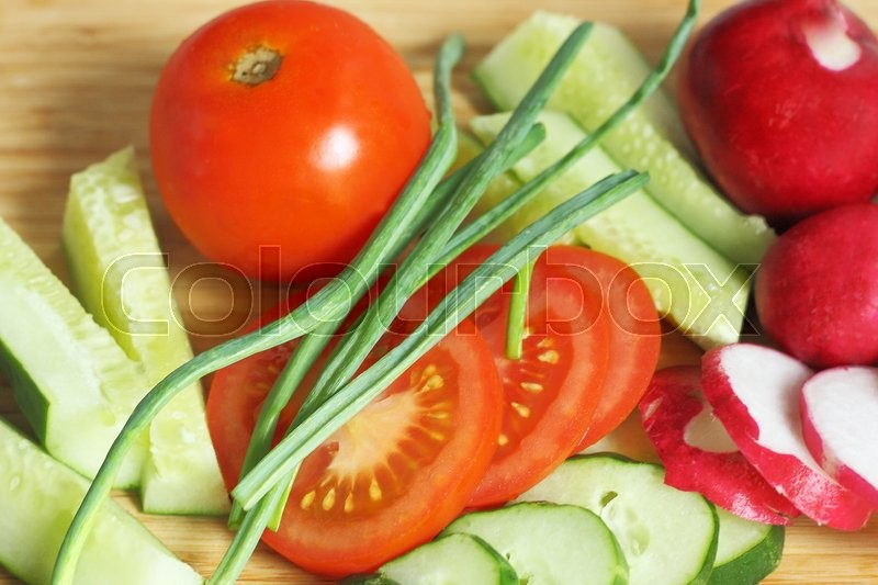 Stock image of 'Ripe vegetables lying on wooden cutting Board.Part of tomatoes, cucumbers and radishes cut into pieces.'